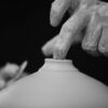 Black and white photo of a close up of hands shaping a narrow neck on a wide pot.