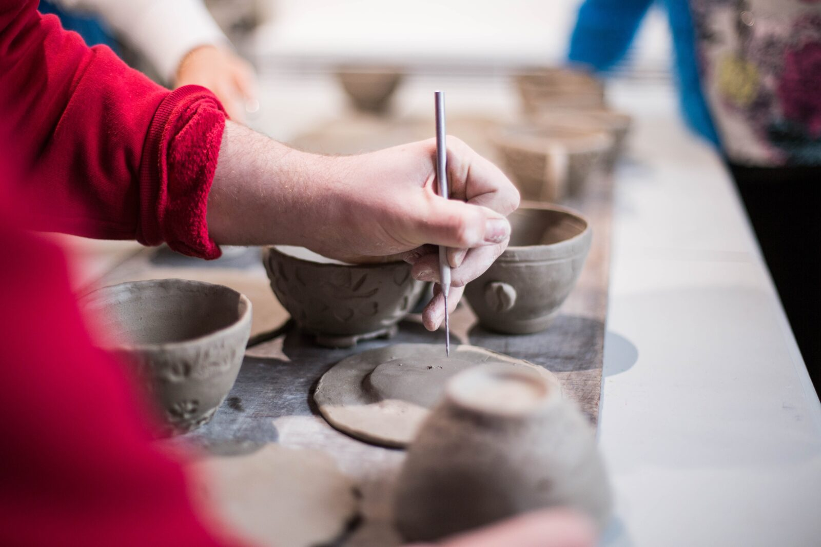 Detail shot of someone wearing a red long-sleeve shirt applying details to clay pots using a metal tool.