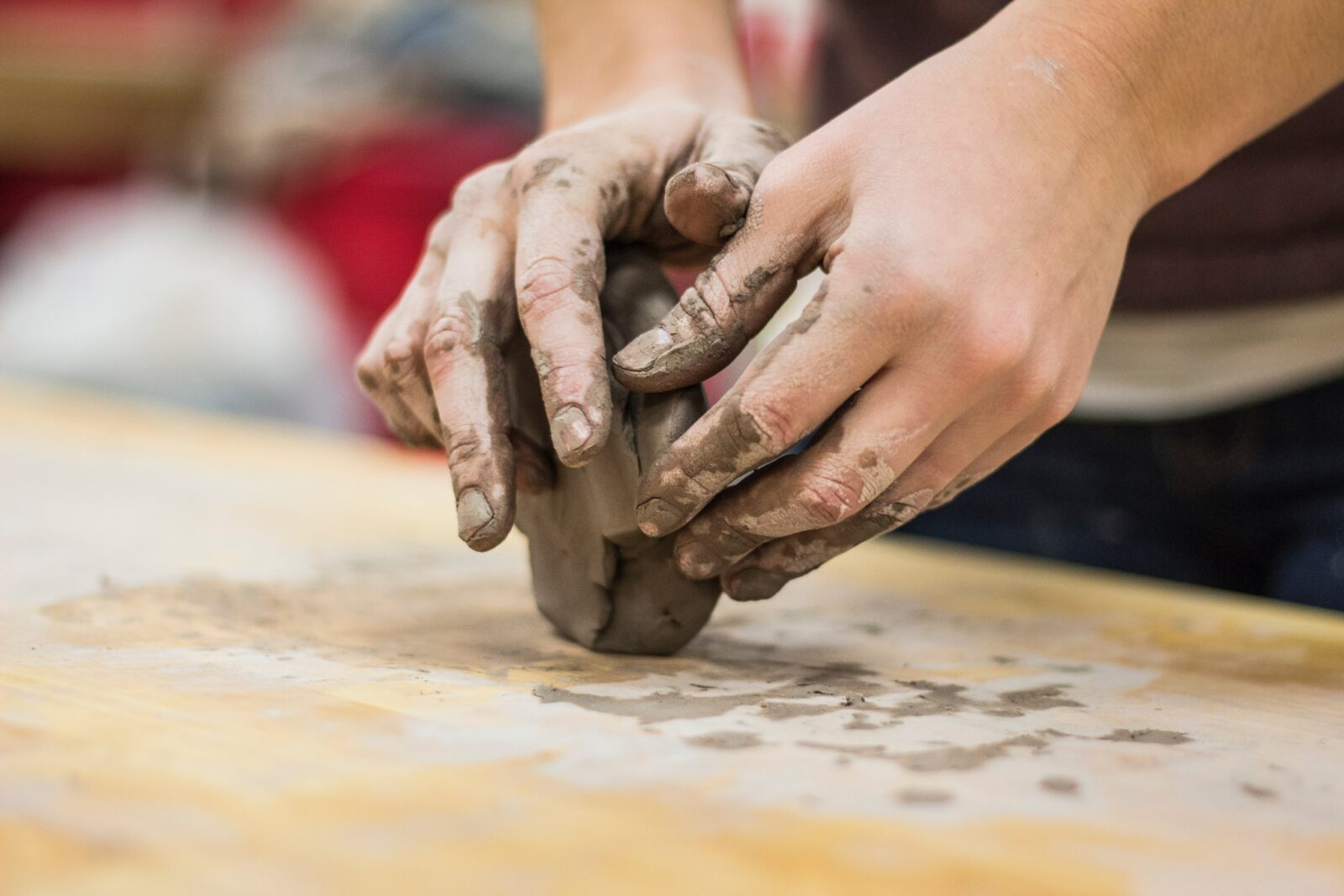 Two hands of a caucasian person working a block of clay on a light-colored wood surface.